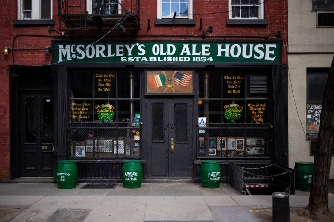 The outside of McSorley's has a green sign and shamrocks