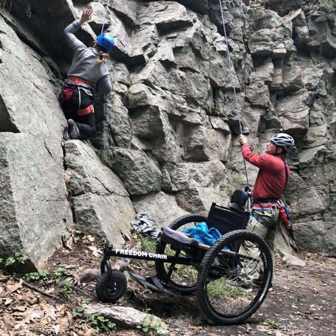 A woman in a wheelchair rock climbing