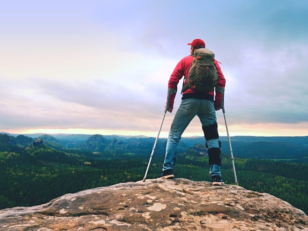 Man using crutches hikes a mountain