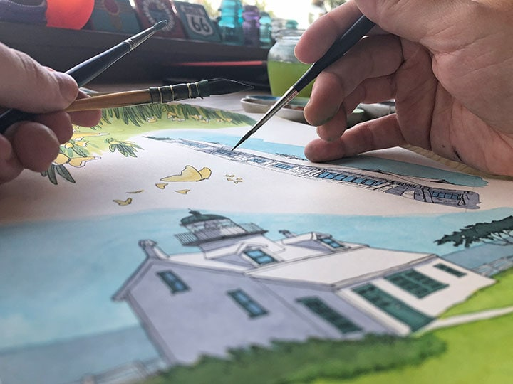 Chandler O'Leary paints a picture of a lighthouse.