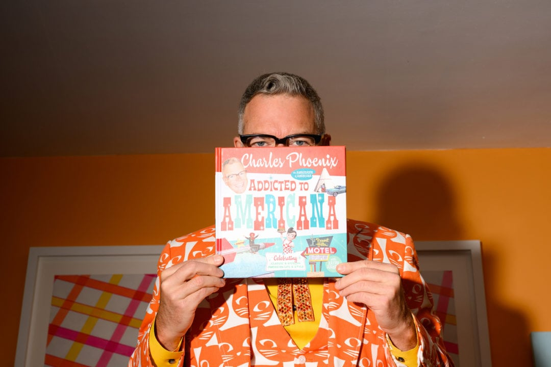 Charles Phoenix, in a bright orange cat-print suit, poses with his most recent book, 'Addicted to Americana.'
