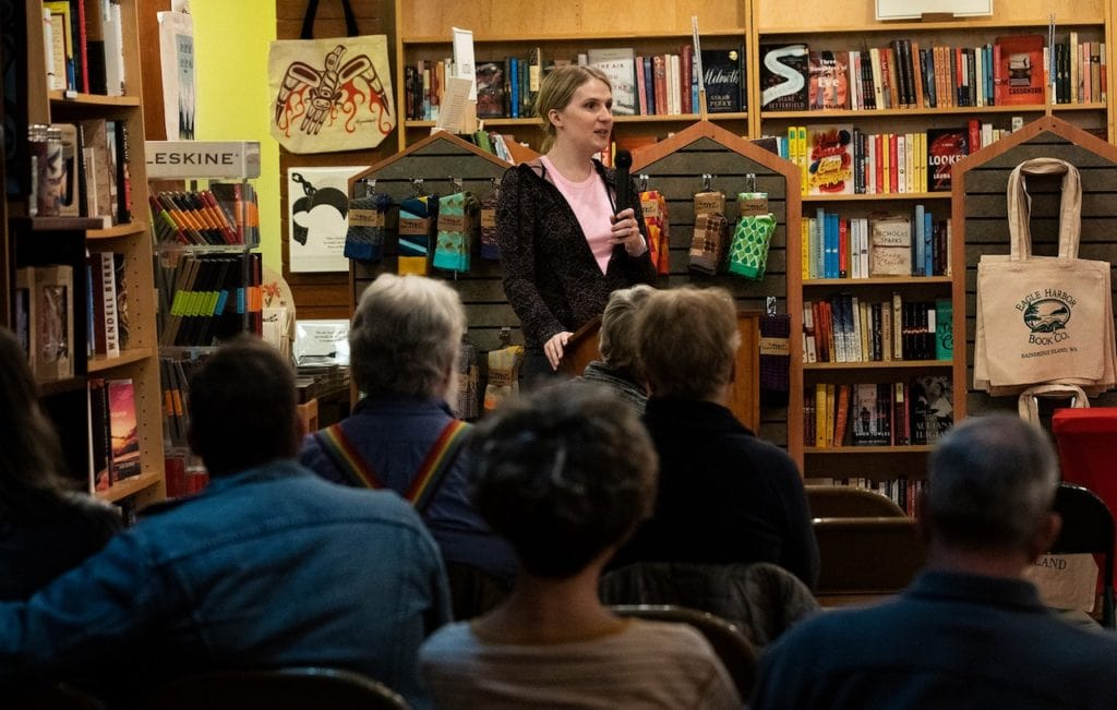 Samantha Allen stands in a crowded bookstore, speaking to a listening audience.