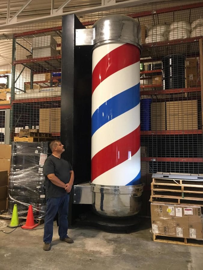Jim Bolin stands next to a giant barber's pole