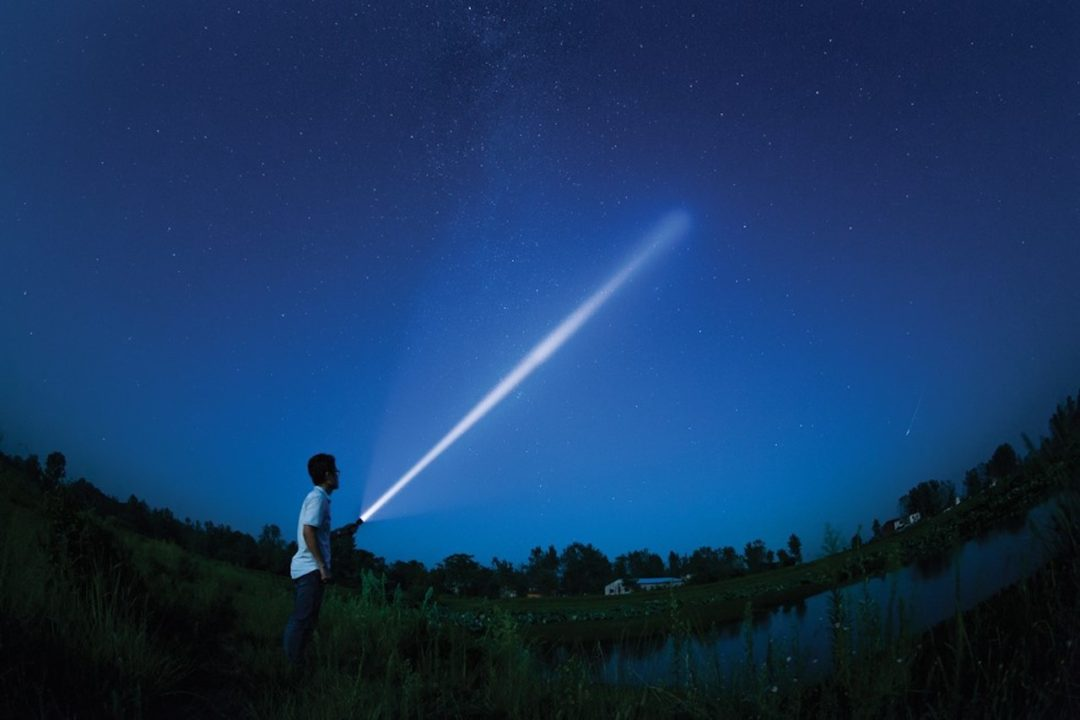 a guide with a flashlight points up at the night sky