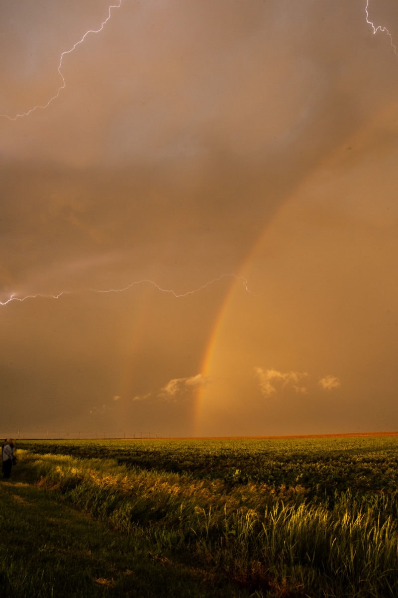 lighting and a double rainbow over a grassy field