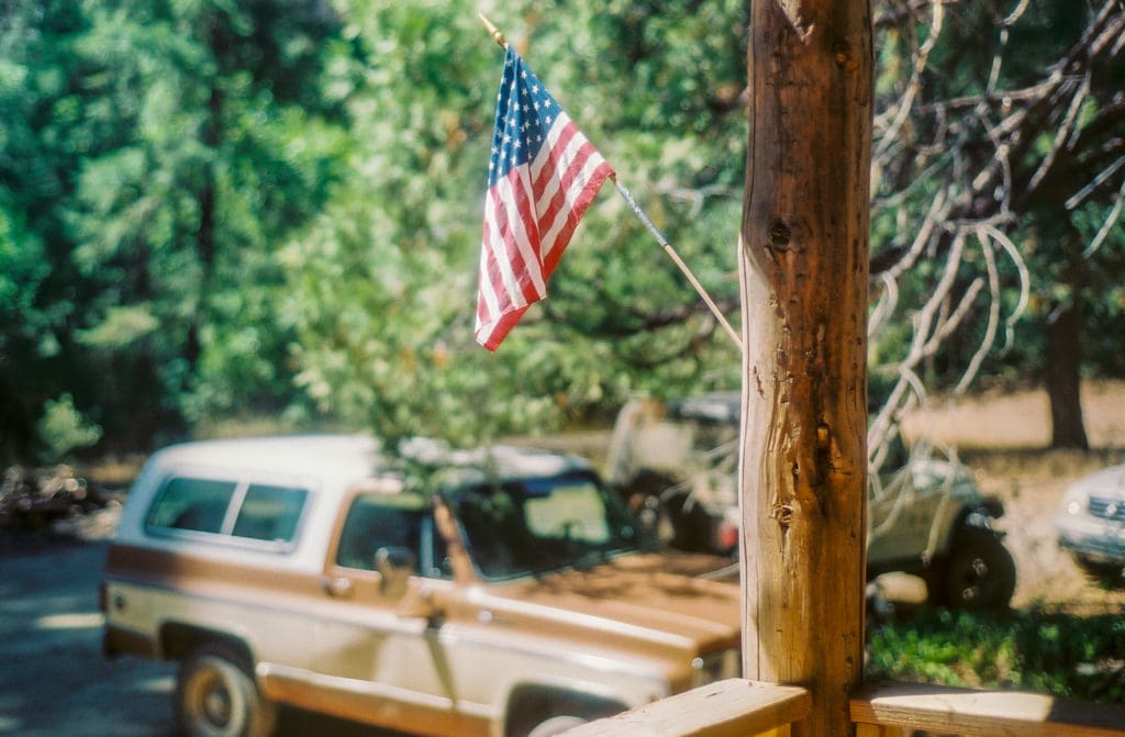 American flag on the porch of the Gin Mill, Shirley's truck in the background