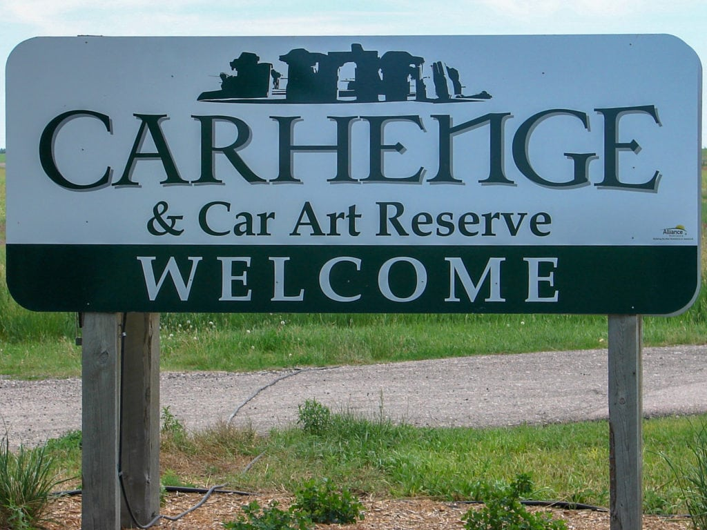 A sign welcomes visitors to Carhenge and Car Art Reserve.