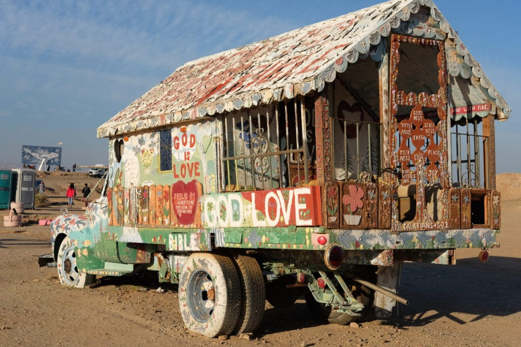 An elaborately painted truck sits in front of Salvation Mountain.