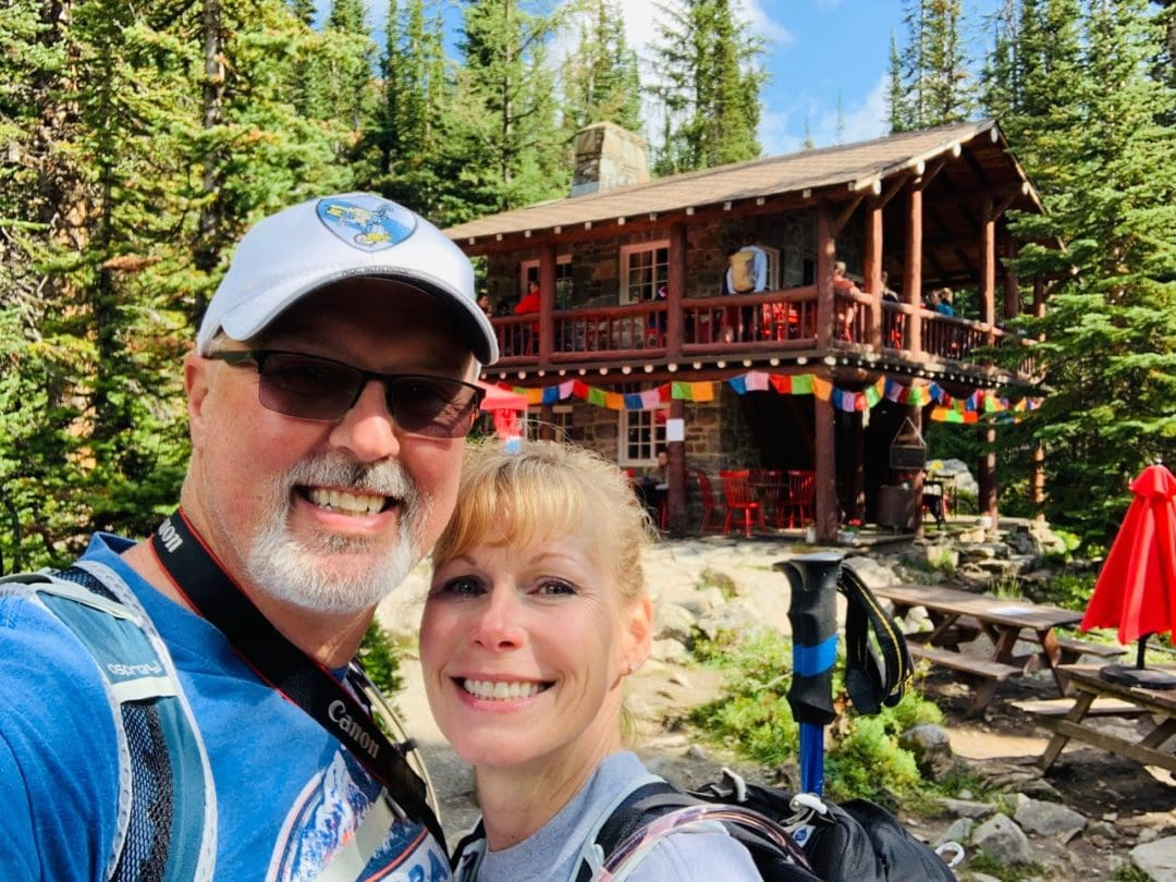 Selfie of hiking couple wearing backpacks in front of old wooden cabin covered in flags and surrounded by pine trees