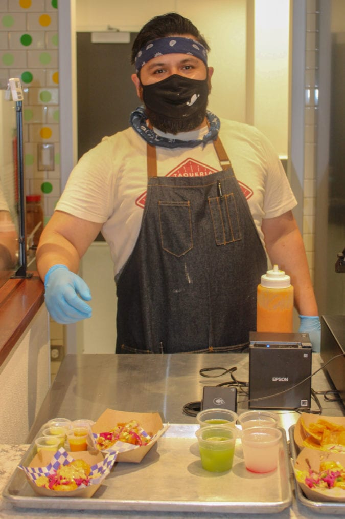 A restaurant worker at Dr. Murphy's Food Hall, wearing gloves, a face mask, and a gown, stands in front of a tray of food.
