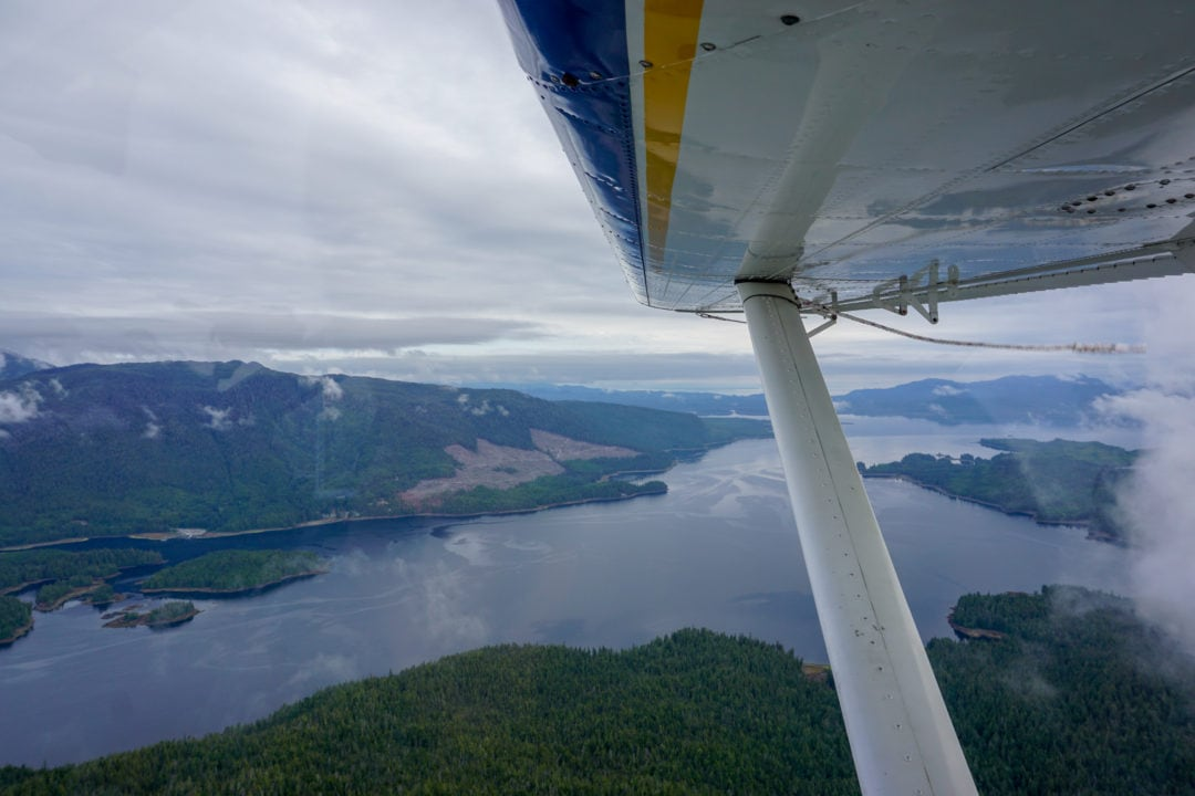 The view from beneath the wing of a float plane, looking out over water and green hills.