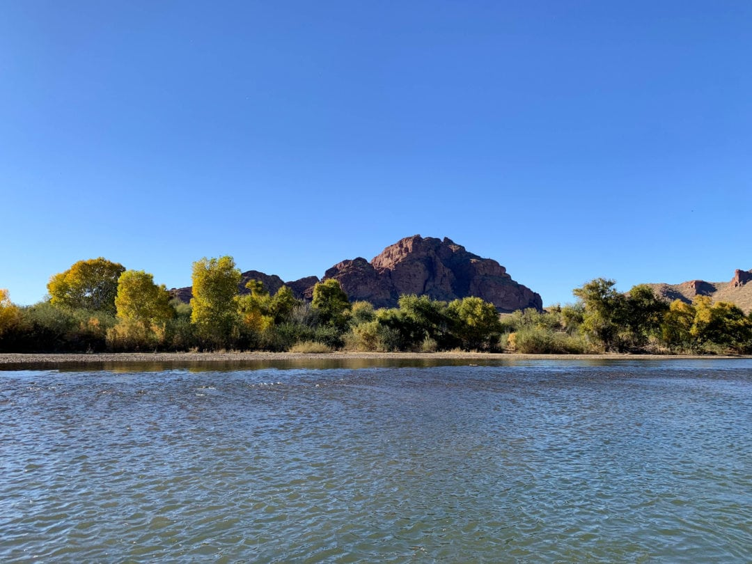 Red rock mountain in the background with green trees along wide river