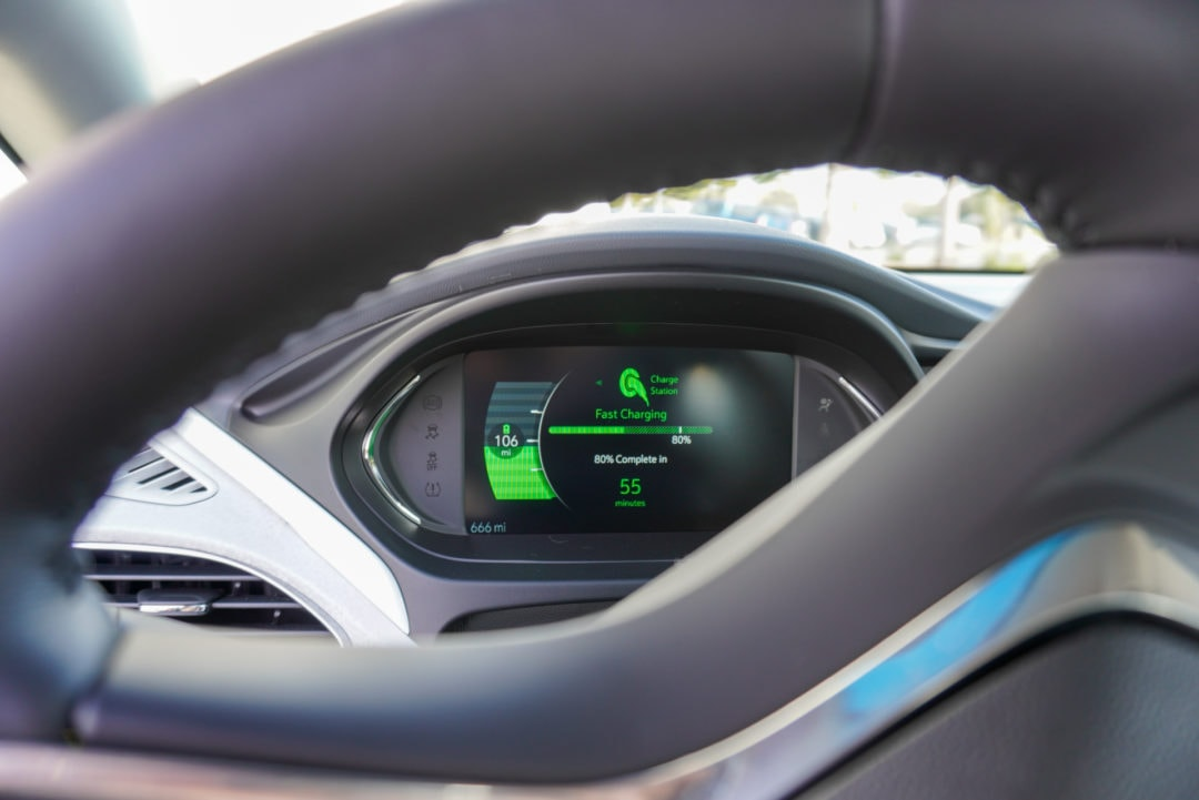 "EV dashboard lit up with a charging message: ""80% complete in 55 minutes"""