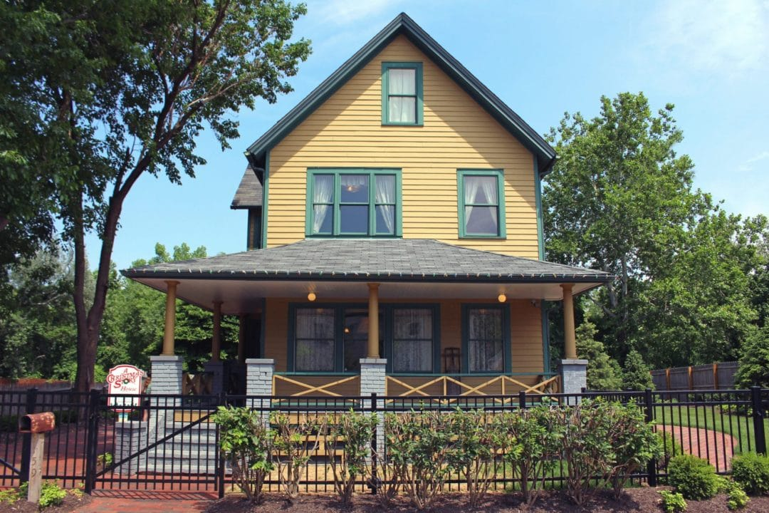 The yellow, three-story house from A Christmas Story, surrounded by a neat lawn and a black fence.