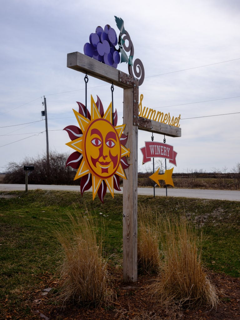 Wooden post with yellow sun hanging off it and sign that says Winery with a yellow arrow pointing