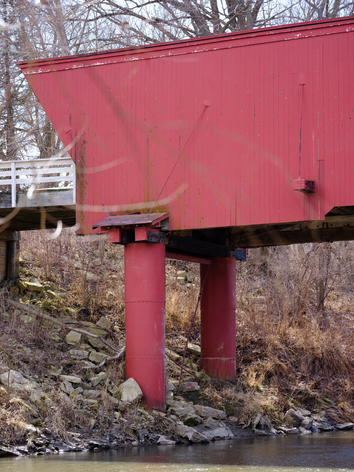 Close up with red covered bridge pillars over rocky creek
