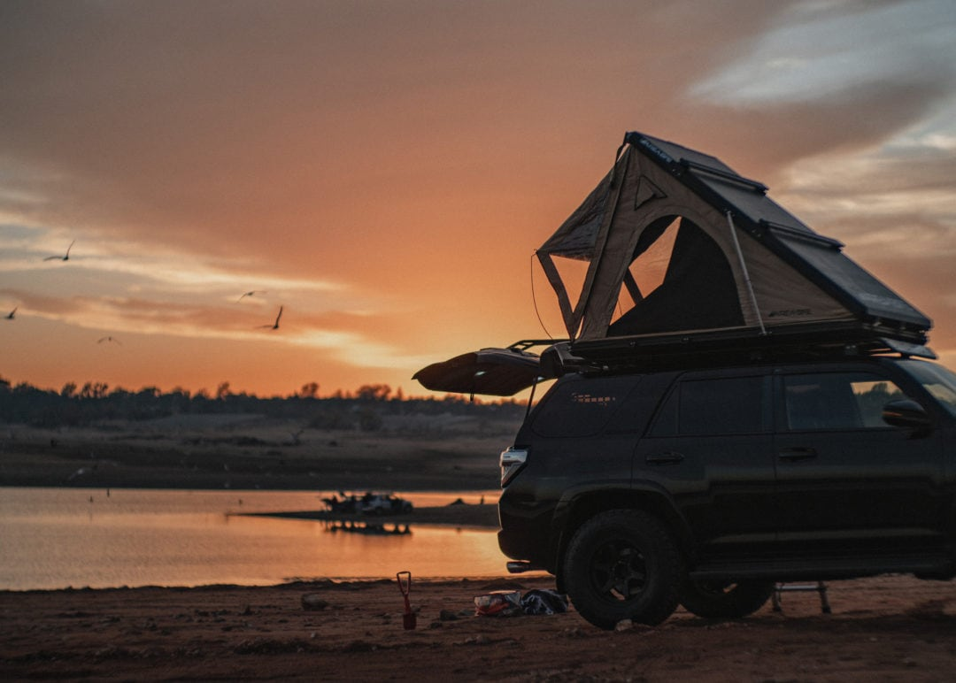 Toyota 4Runner along the edge of a lake at sunset with hatch open and rooftop tent on top of car