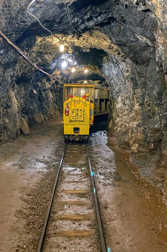 A bright yellow train coming through a mine tunnel
