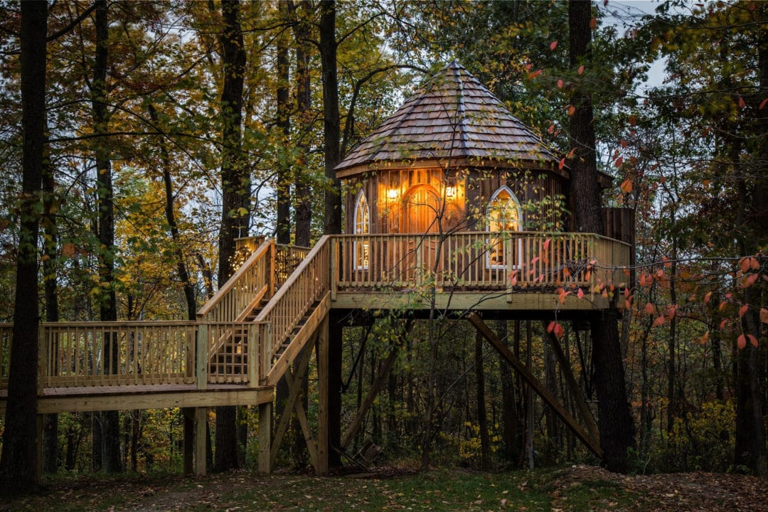 A wooden treehouse set in the woods with a wooden walkway and staircase