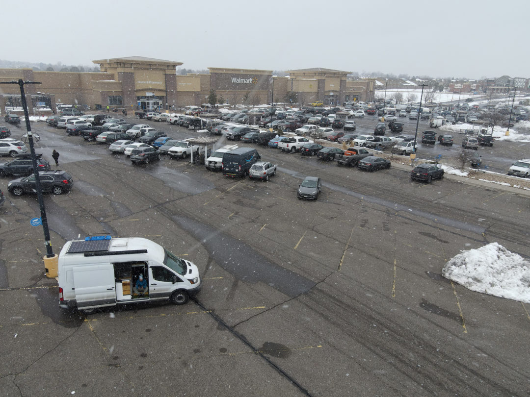 A white van is parked in a full Walmart parking lot as it snows