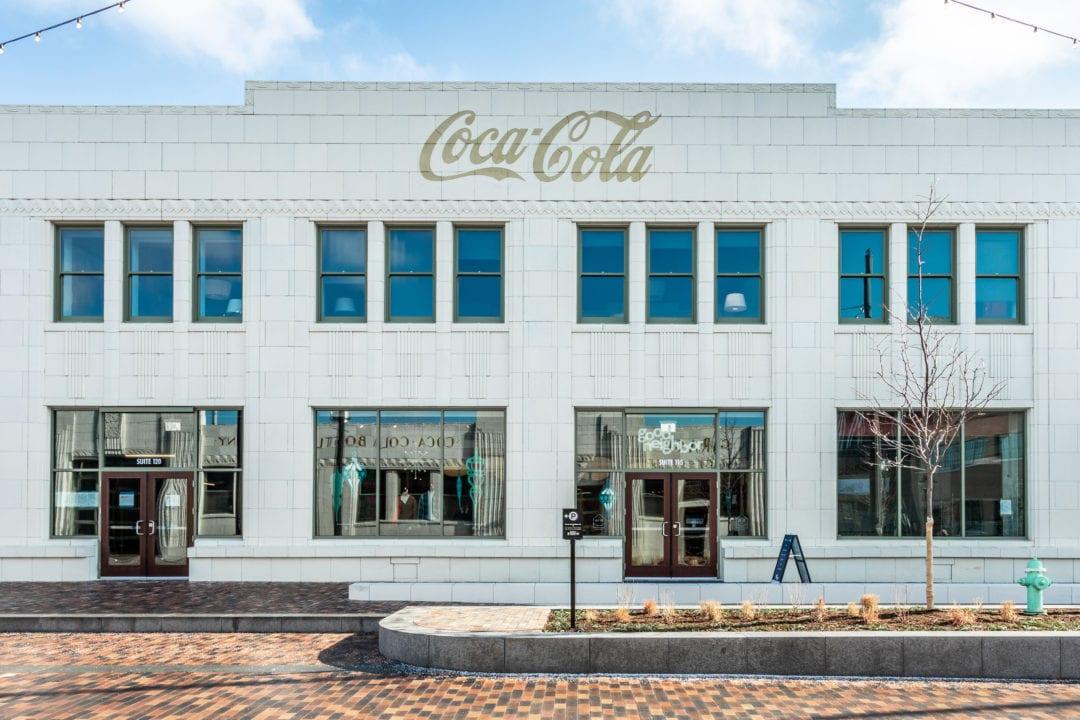 a white art deco building with gold coca-cola logo