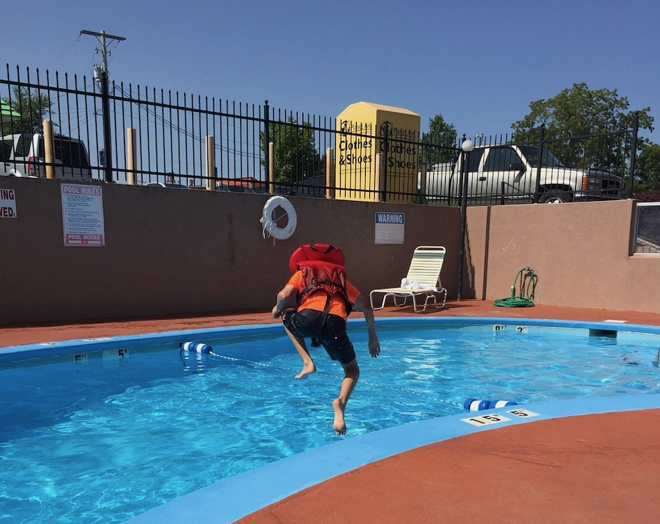 Boy in life vest jumping into pool