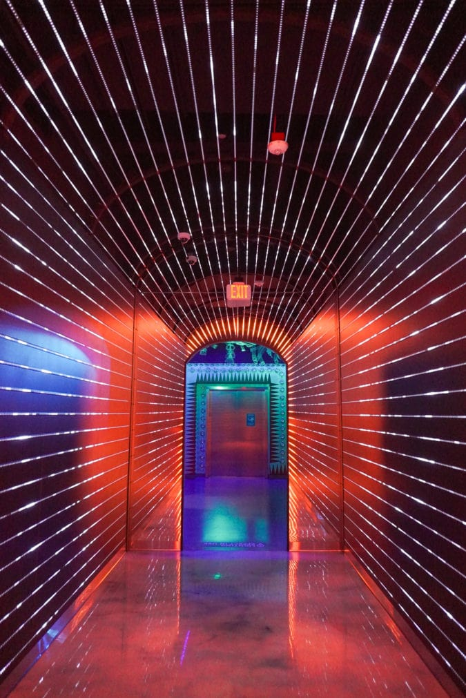 A brightly lit corridor where the light changes color.