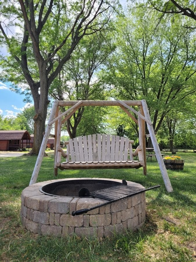 Wooden swing in front of a stone fire pit surrounded by green trees and blue skies