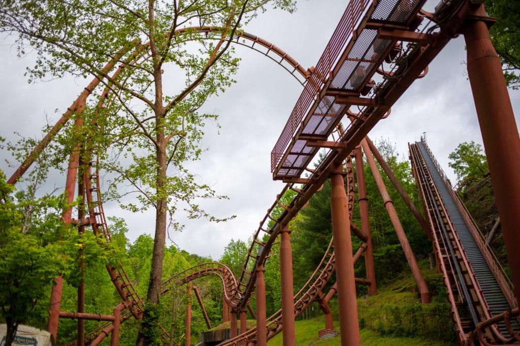 an orange steel rollercoaster track set against a lush green backdrop