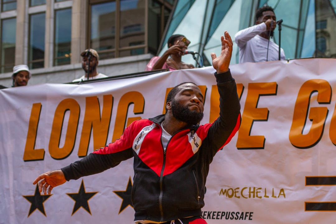 """A Black man dances in front of a banner that says """"Long Live GoGo"""""""