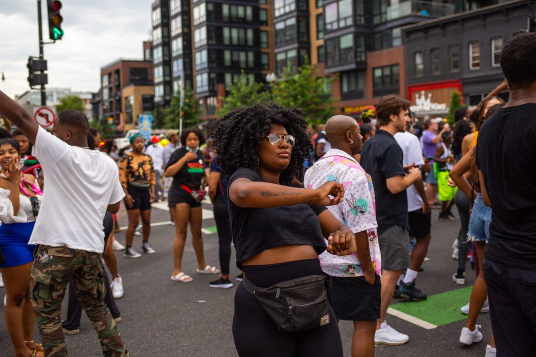 """A Black woman with a """"wild and wonderful"""" tattoo on her forearm dances in the street"""