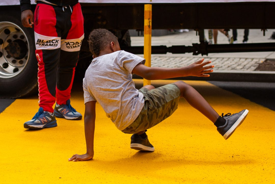 a Black boy shows off his dance moves on a painted yellow street