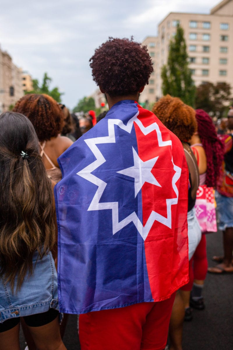 A man is draped in a red, white, and blue Juneteenth flag