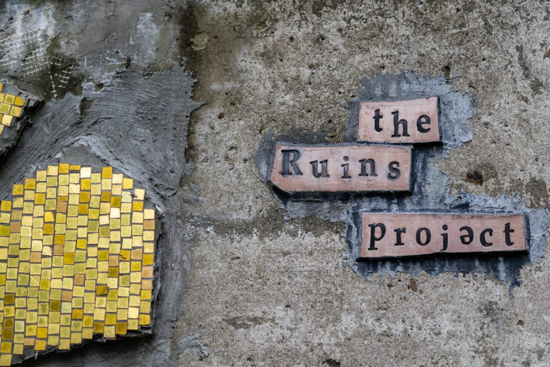 """a yellow mosaic next to a sign that reads """"the ruins project"""""""