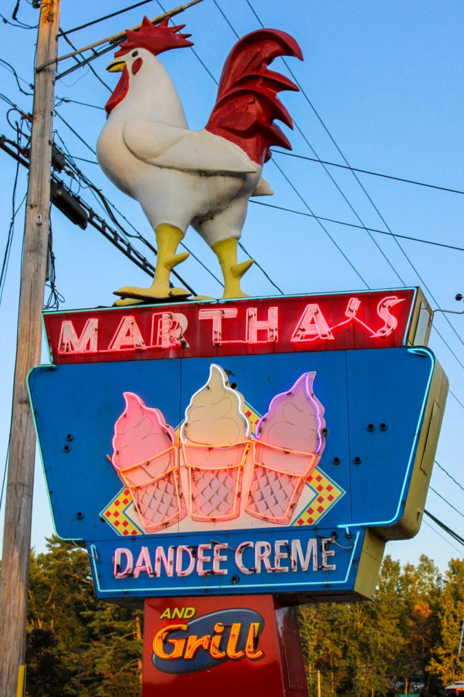 """a neon sign topped with a rooster that says """"martha's dandee creme"""""""