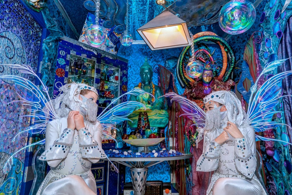 Two women dressed in white costumes with wings look at each other in a blue-tinted room